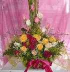 Mixed roses, solidago, genest, limonium, and greens in a basket