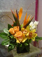 Bird of paradise, cymbidium orchids, lillies, iris, green berries, alstroemeria, roses, and curly willow
