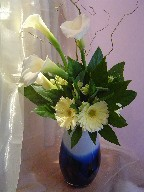 Calla lillies, gerbera, alstroemeria, curly willow, and fatsia japonica