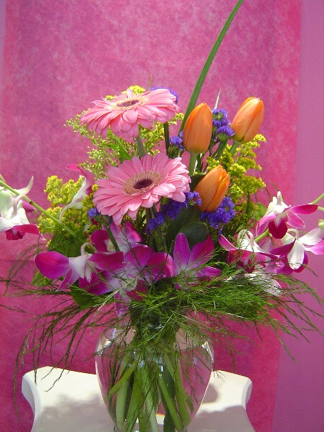 Gerbera, dendrobium orchids, tulips, solidago, statice and monkey grass