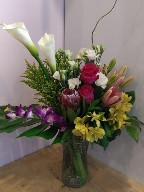 Calla lillies, protea, roses, lisianthus, asiatic lillies, dendrobium orchids, alstroemeria, solidago, monstera, and branch