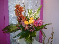 Cymbidium orchids, snapdragon, roses, lillies, alstroemeria, monstera, and curly willow