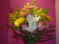 Gerbera, lillies, tulips, roses, solidago, and waxflowers