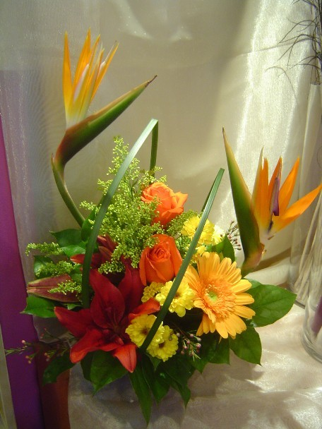 Bird of paradise, roses, gerbera, lilies, daisies, solidago, and monkey grass