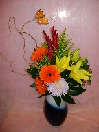 Gerbera, lillies, spider mum, solidago, hypericum, curly willow, and greens