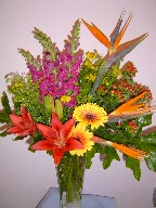 Snapdragon, bird of paradise, coffee beans, helenium, gerbera, lillies, solidago, and philodendron