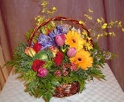 Oncidium orchids, agapanthus, tulips, roses, wax flowers, gerbera, alstroemeria, and asiatic lillies in a basket
