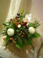 Cymbidium orchid, lillies, snowcap, hypericum, alstroemeria, cedar, and Christmas decorations