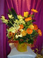Shocking lillies, orchids, gerbera, roses, pompoms, coffee beans, solidago, and sago palm