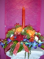 Roses, carnations, lillies, berries, orchids, pine, and Christmas decorations