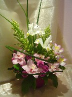 Cymbidium orchids, iris, alstroemeria, pompoms, solidago, monkey grass, and greens