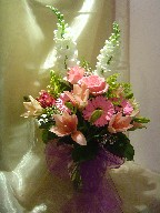 Snapdragon, roses, gerbera, lilies, alstroemeria, solidago, and waxflowers
