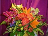 Roses, lillies, statice, solidago, orchids, fresia, pompoms, and monkey grass