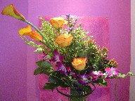 Mango calla lillies, roses, orchids, coffee beans, monkey grass, solidago, and monte casino blue