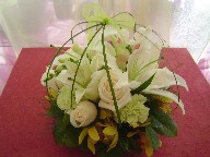Casablanca, ivory roses, snapdragon, green carnations, mini cymbidium, and bear grass