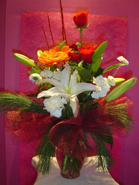 Lilies, carnations, roses, gerbera, aster, pine, and Christmas branch