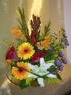 Roses, celosia, gerbera, lillies, daisies, pompoms, leucadendron, solidago, and monkey grass