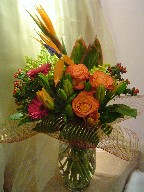 Bird of paradise, roses, gerbera, lillies, hypericum, solidago, and cordyline
