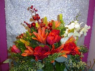 Roses, tulips, lillies, red and green berries, pine, dendrobium orchids, seed eucalyptus, and Christmas ornaments