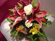 Stargazer, roses, freesia, solidago, waxflowers, and orange carnations