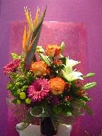 Bird of paradise, roses, gerbera, lillies, pompoms, solidago, coffee beans, and waxflowers